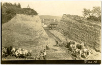 Teams of horses and workers cutting through hill to construct Harris Avenue