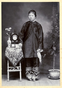 Formal full body studio portrait of young unidentified Asian woman in traditional dress