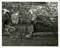 Bellingham Coal Mines - Three miners with headlamps in coal mine, standing next to mining rail car on tracks