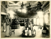 Possibly the interior of polynesian-themed exhibition with displays of goods and produce, a scale model of a three-masted ship made of straw, and straw-crafted décor