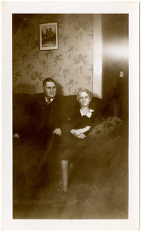 A man and woman sit on a sofa