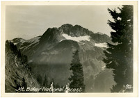 Vista of rocky Mt. Shuksan with glaciers seen from alpine ridge with two men in foreground