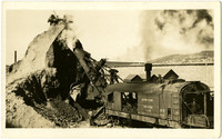 Railcar-mounted steam shovel moves coal from large coal pile