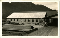 Postcard of long, narrow building of mill or cannery under construction on wooden deck with several structures adjacent, and steep, forested mountains in background
