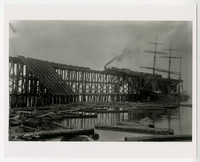 Three-masted ship docked next to high wooden trestle with loaded coal bunkers, logs float in nearby water