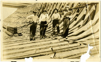 Four men pose inside the newly-laid hull of ship