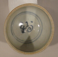 Cup with blue decoration of a character, exterior with floral panels