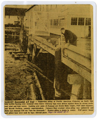 Newspaper clipping of men leaning over pier looking at storm damage