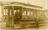 """Uniformed railcar employees with """"Sehome Wharf"""" streetcar at the corner of Dock (now State) St. and Holly St. in Bellingham, WA"""