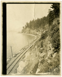 A train travels along tracks of railway that skirts mountainside at shoreline
