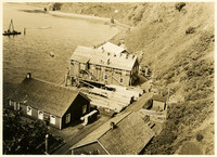 View from above of waterside cannery facilities under construction at base of steep hill