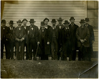 Formally dressed group of men pose for photograph