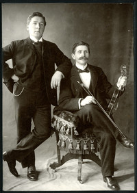 Formal studio portrait of one man seated with violin, one man posing behind him