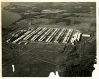 Aerial view of the Intalco Aluminum Plant near Ferndale, showing six large, horizontal smelters and several smaller buildings on the rural site with the water showing in the upper left