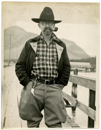 Man wearing cowboy hat, horn-rimmed glasses, and goatee, with a pipe, stands on a dock with mountain in background