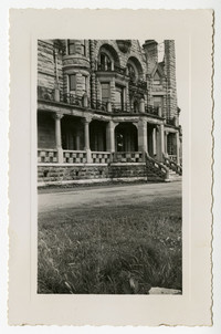 Unidentified building made of sandstone showing entrance flanked by columned porch with balcony above, with several stories, arched and bay window