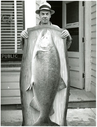 Man holds large plaque mounted with enormous salmon