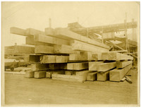 Stack of large wood beams at lumber yard with millworks in background
