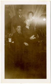A young couple stand behind an older seated couple in a private parlor