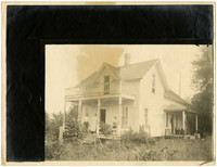 A woman, a man, and a boy stand on porch of two-story Gothic revival farmhouse with upper balcony