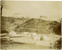 Several people, tents, and canoes on beach with wooden walkway leading up the bluff to buildings of early Bellingham, WA