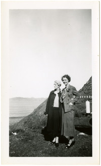 Two women stand near road on bluff overlooking water