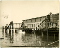 "Small fishing vessel ""Ruth"" tied to a pier with two-story warehouse, possibly a fish processing or canning plant"