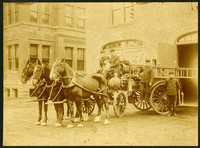 Three draught horses hutched to fire wagon with four uniformed firemen and a dog, outside a brick firehall