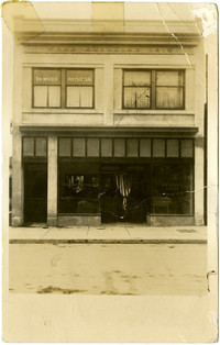 Front exterior of office building of Dr. Wood, Physician, and The Lynden Tribune with American flag in doorway