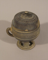 Waisted lidded cup with handle with row of five rectangular slots in stem