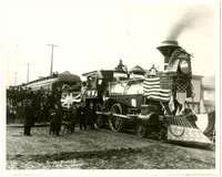 Several men and a dog stand next to locomotive of steam train festooned with American flags, with a crowd of people on platform behind, honoring the first train to arrive in Fairhaven, WA, 1891
