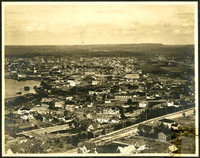 Vista of downtown Bellingham and surrounding neighborhoods with several identifiable commercial and residential buildings, including Morse Hardware, The Fair, Lighthouse Theatre, B.B. Grocery Co., G.N. (Great Northern) Furniture Co., City Hall, Courthouse