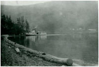 """Steamboat """"Marguerite"""" pulls up to shore of Lake Whatcom, with forested hills in background"""