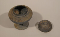 Waisted lidded vessel with three rectangular slots in stem