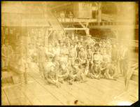 Large group of unidentified men, probably mill workers, sitting and standing on a wooden deck with the mill behind them