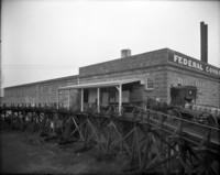 Federal Condensed Milk Co. building showing both truck and horse-drawn wagon delivery vehicles