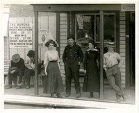 Two women and two men stand on boardwalk in front of store next to billboard advertising ferry rides