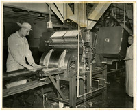 Man and woman cannery workers stand next to large skinning machine with motorized drum at center, skinning two salmon filets