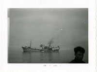 Japanese gillnetter in calm water, with head of man in lower right corner