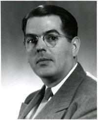 Studio portrait of man in suit and spectacles