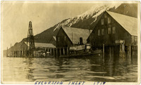 Warehouses on docks with tugboat at Excursion Inlet
