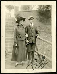 Teenage boy in arm with older woman pose outdoors on wooden walkway below stairway