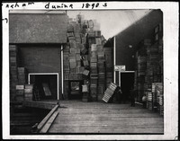 "A huge pile of wooden crates piled high with five men perched among the crates all the way to the roof of the adjacent building where there is a sign that says ""Positively No Admittance"""