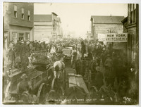 Very crowded street scene in Nome, Alaska, with throngs of men, a few women, horses and wagons filling the street