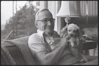 Unidentified man, likely Galen Biery, seated with small dog