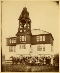 Students and teachers pose outside three-story Central School with prominent bell tower