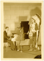 An unidentified man (probably Gunnar Anderson) at piano with a second individual dressed in Native American regalia