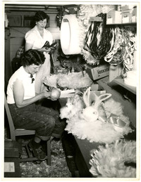 Two women in crafts workshop, assembling possibly Easter-related items from feathers, bows, bunny heads, pipe cleaners