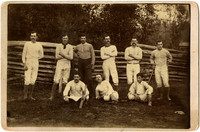 Three men seated, six standing, pose in baseball outfits in front of split-rail fence