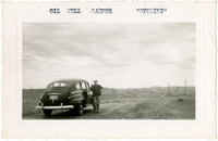 Man poses next to car before barren landscape dotted with oil derricks